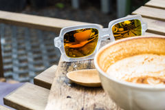 Sunglasses refection of coffee cup. On wooden table Stock Images