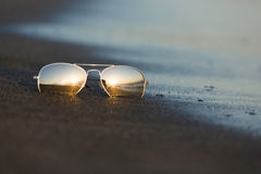 Sunglasses reflect the light of the setting sun at sandy beach Royalty Free Stock Photo