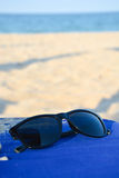 Sunglasses on restaurant table in vacation at the sea side Royalty Free Stock Photo