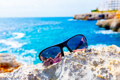 Sunglasses on  rock near the sea Royalty Free Stock Photography