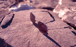 Sunglasses on a rock royalty free stock photo