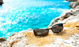 Sunglasses on a rock by the sea Royalty Free Stock Photography