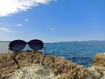 Sunglasses on the rock under blue sky in Sado island, Japan royalty free stock photography