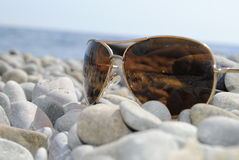 Sunglasses on the rocks. Sunglasses lying on a pebble beach royalty free stock images