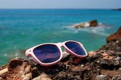Sunglasses on a rocky beach Stock Photos