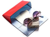 Sunglasses with round lenses in a composition with a red case stock photo