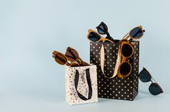 Sunglasses sale concept. Different sunglasses in shoping bags on blue background. Fashion summer accessories. Copy space. For text royalty free stock photography