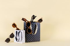 Sunglasses sale concept. Different sunglasses in shoping bags on yellow background. Fashion summer accessories. Copy space. For text stock photo