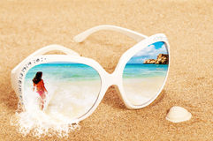 Sunglasses In The Sand. Concept image of summer holidays with beach scene in sunglasses on sand Royalty Free Stock Photography