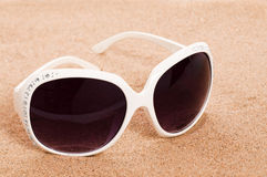 Sunglasses In The Sand. White sunglasses in golden sand, holiday vacation concept Stock Photo