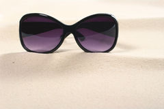 Sunglasses on Sand. Purple colored sunglasses on sand dunes with copy space (Selective Focus, Focus on the sunglasses Stock Photo
