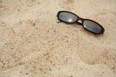 Sunglasses in the sand. Pair of sunglasses sitting in the sand at the beach stock image