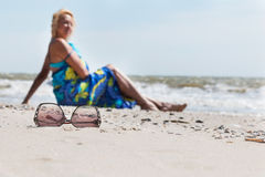 Sunglasses on the sand  and beautiful woman with blue sarong Royalty Free Stock Images