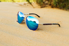 Sunglasses on the sand in the desert. Royalty Free Stock Image