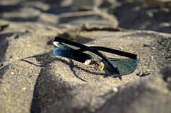 Sunglasses on the sand. Sunglasses lying in the sand on the beach by the sea Royalty Free Stock Photo