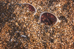 Sunglasses in sand. Purple lens sunglasses. Under hot tropical sun. See life in new colors Royalty Free Stock Photos