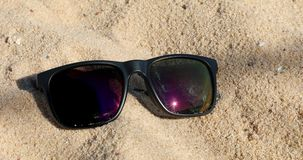 Sunglasses On The Sand. Reflecting Black Sunglasses On The Sand At The Beach, Summer - Close Up View - DCi 4K Resolution stock video footage