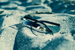 Sunglasses on the sand. Of the sea Royalty Free Stock Images