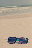 Sunglasses in the sand on the seashore. vacation time Royalty Free Stock Images