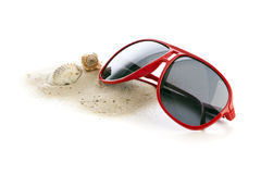 Sunglasses, sand and shells. Red sunglasses on heap of sand with shell and seasnail isolated Stock Photo