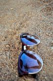 Sunglasses in sand. Sunglasses in the sand at the beach Royalty Free Stock Image