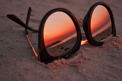 Sunglasses on the sand with the sunset royalty free stock photo
