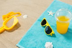Sunglasses, sand toys and juice on beach towel royalty free stock photography