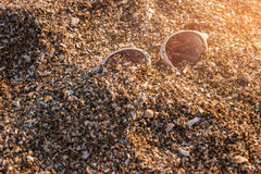 Sunglasses in the sand. White frame sunglasses. Light of tropical sun. See new colors of life Royalty Free Stock Photo
