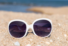 Sunglasses on the sand. Women's white sunglasses in the sand overlooking the sea, the concept of summer beach holidays Stock Images