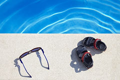 Sunglasses and Sandals at the swimming pool Royalty Free Stock Image