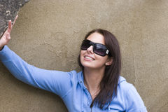 Sunglasses and Sandstone. A pretty young woman in sunglasses smiles in front of a sandstone rock Royalty Free Stock Images