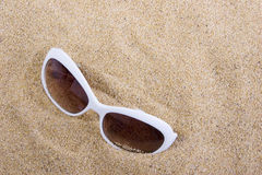 Sunglasses on sandy beach Stock Image