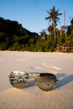 Sunglasses on sandy beach over tropical island background Stock Images