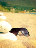 Sunglasses on a sandy beach Stock Images