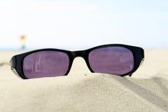 Sunglasses on sandy beach Stock Image