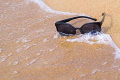 Sunglasses and sandy coast with wave Stock Images