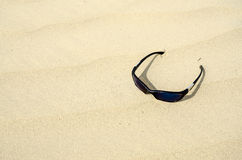 Sunglasses in sandy waves. Sunglasses sitting in the bright golden sand Stock Images