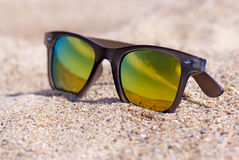 Sunglasses on the sand, close up view, beach. Colorful summer picture: close up view on a bright brown-gold color sunglasses lying in the sand on a beach. Wet Stock Photos