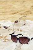 Sunglasses sarong sandals on the beach Royalty Free Stock Photo