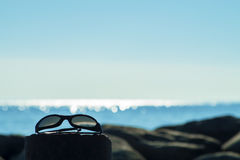 Sunglasses by the sea with copy space Stock Photo