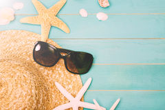 Sunglasses with sea shells and straw hat. On light blue wooden background royalty free stock images