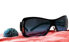 Sunglasses and seashell on a red beach towel Royalty Free Stock Photography