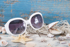 Sunglasses with seashells and fishing net and a wodden blue back Royalty Free Stock Image