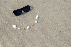 Sunglasses and shells create a smile to peep Royalty Free Stock Photo