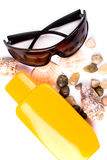 Sunglasses, shells and lotion Royalty Free Stock Photos