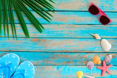 Sunglasses, shells, starfish and slipper on wood background. stock image