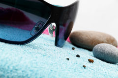 Sunglasses and shingle on a beach towel. Perspective view of a composition with a pair of fashion sunglasses and some shingle on a blue beach towel, detail Stock Photo