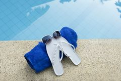Sunglasses shoes towel pool blue water Royalty Free Stock Photography