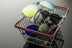 Sunglasses in the shopping box. Sunglasses various models and colors stacked in a shopping basket Royalty Free Stock Photography