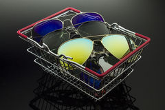 Sunglasses in the shopping box. Sunglasses various models and colors stacked in a shopping basket Stock Photography